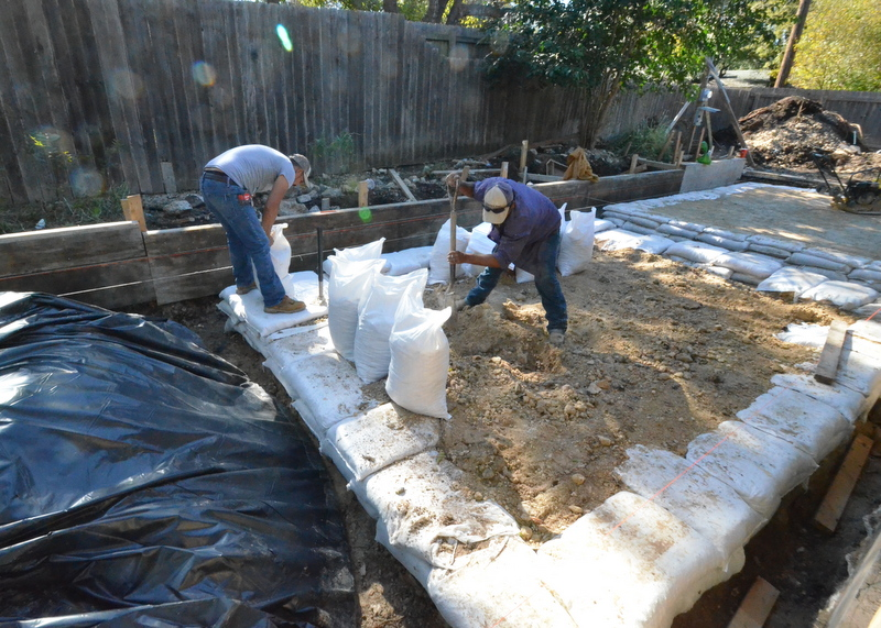 At 10 am, Cezar Ernesto, left, and Ernesto Jovini are packing sandbags with roadbase for the middle island of the new garage foundation.
