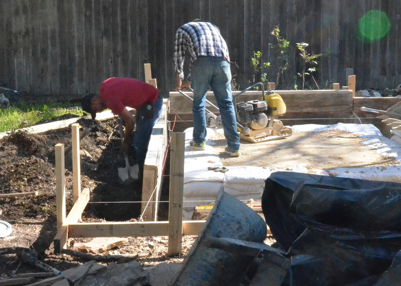 After bringing the road base up to the proper height, they begin shifting the form to square out the back of the garage foundation.