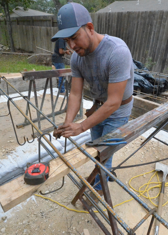 At a second jig, Ernesto assembles the bends of rebar into an assembly ...