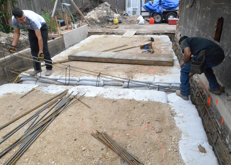 That Ely, left, and Jose Luis, right, place the steel formwork into a trench for the garage footings.