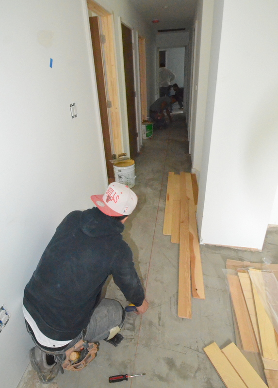 By 2 pm, they are pulling a string line tight down the middle of the upstairs hallway -- and snapping a chalk line to follow with the wood.