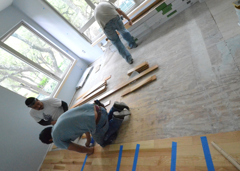 The master bedroom is started. Blue painters tape helps to hold the boards tightly together, to prevent the glue from lubricating the planks apart.