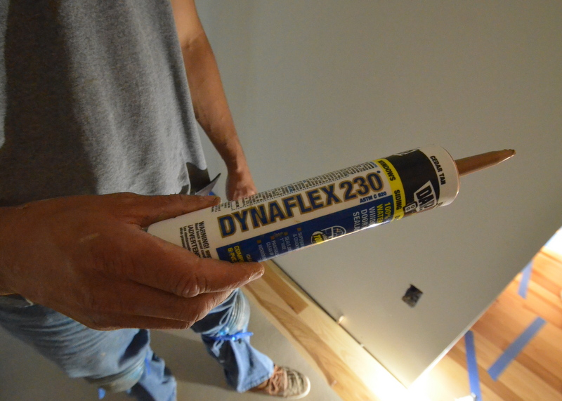 Ivan holds a tube of the colored caulk used to close gaps between the wood planks and tile floors.