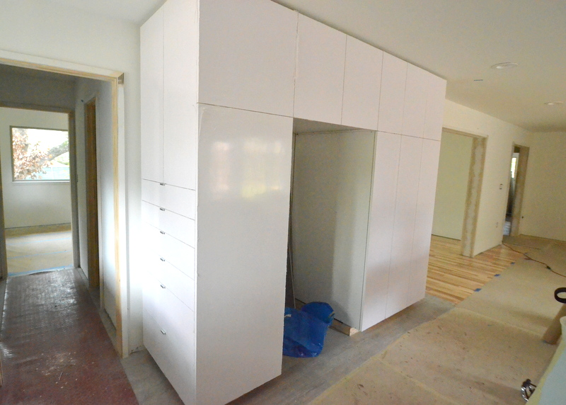 Here's the storage cabinet at left, with all the other doors mounted. The refrigerator slots into the open bay. All the white melamine surfaces are covered by dull plastic protectors.