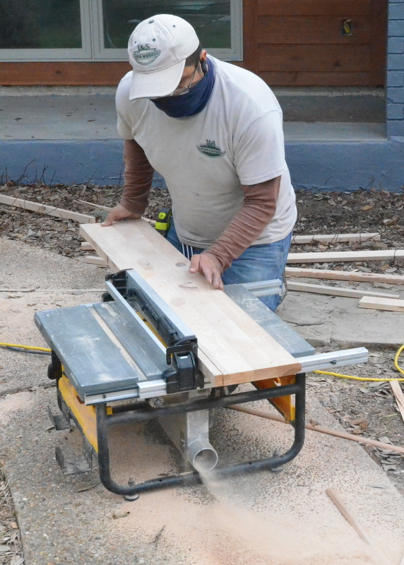 Outside, Luis trims a narrow strip of hickory from a tread that is being used to fill gaps between the tread and the riser ... for this, he's working on a slightly larger, slightly more powerful Dewalt table saw, not his lightweight Black & Decker ...