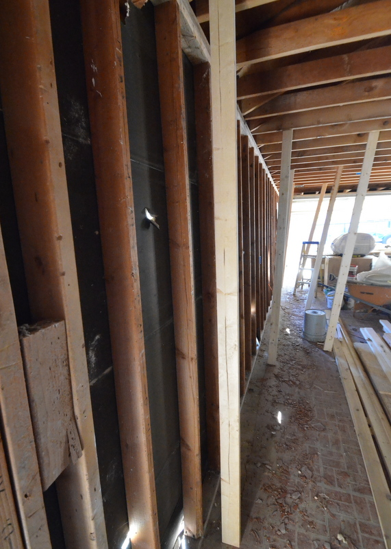 After whacking with a sledgehammer, the back wall of the garage leans against the temporary braces. The wide-angle lens distorts perspective, but the footing of the wall is now offset 3 to 4 inches from the top plate.