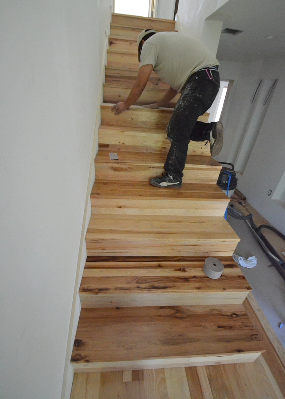 What the stairs look like with one coat of sealer and the first coat of water-based, clear polyurethane -- with Luis working his way to the landing as he sands each step.
