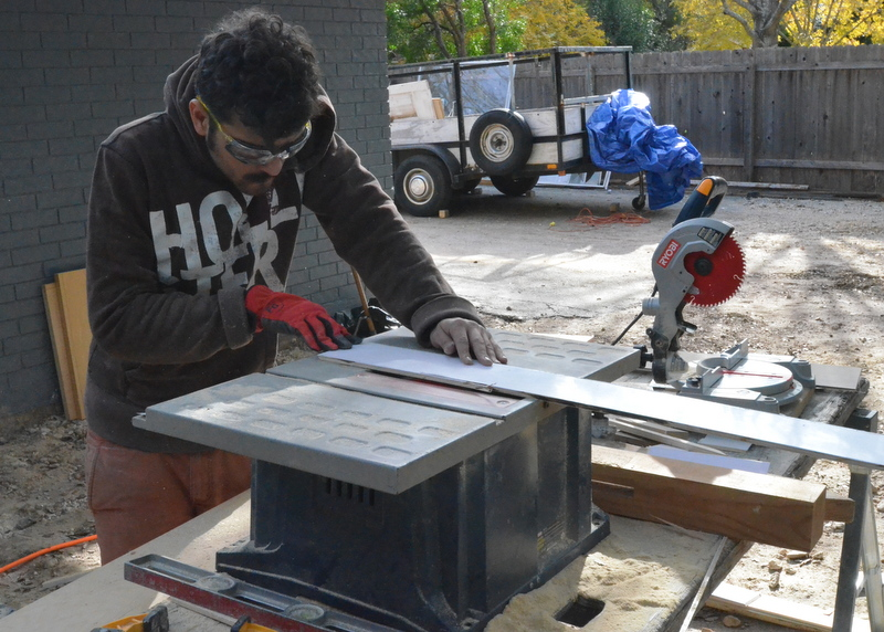 Working at the table saw outside, Yitzhak slowly cuts the 1/4-inch-thick material to size.