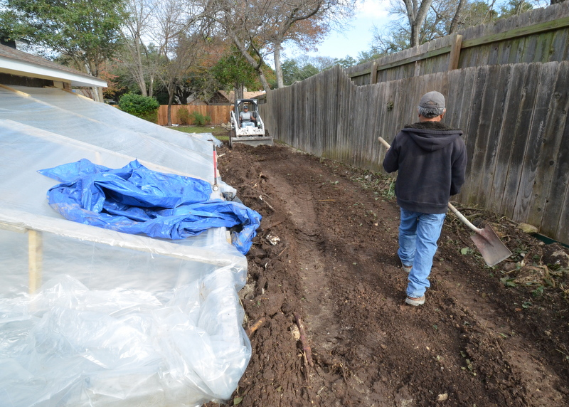 Gilsa used a Bobcat to clear the debris out from behind the garage and to grade the remaining dirt properly for drainage. The bare dirt will be covered with landscape fabric to prevent weeds, which will then be covered with three inches of black rock.