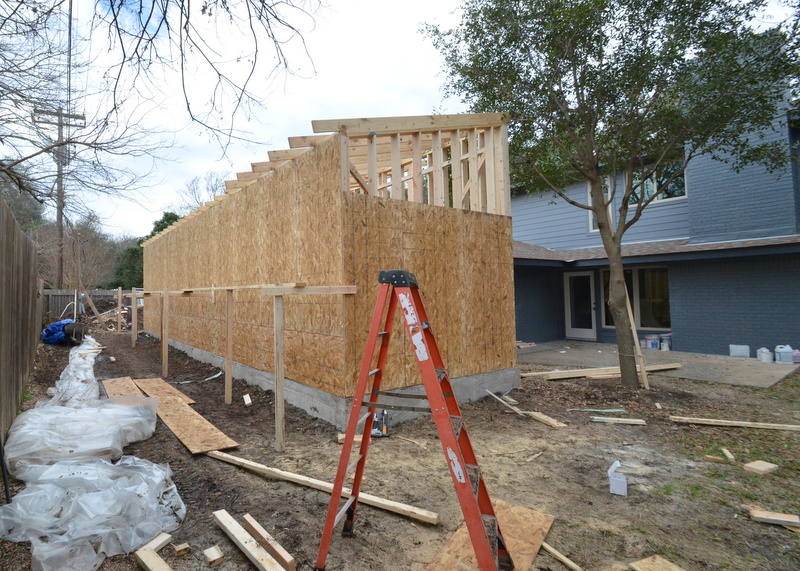 OSB sheathing covers the back and side walls of the garage box.