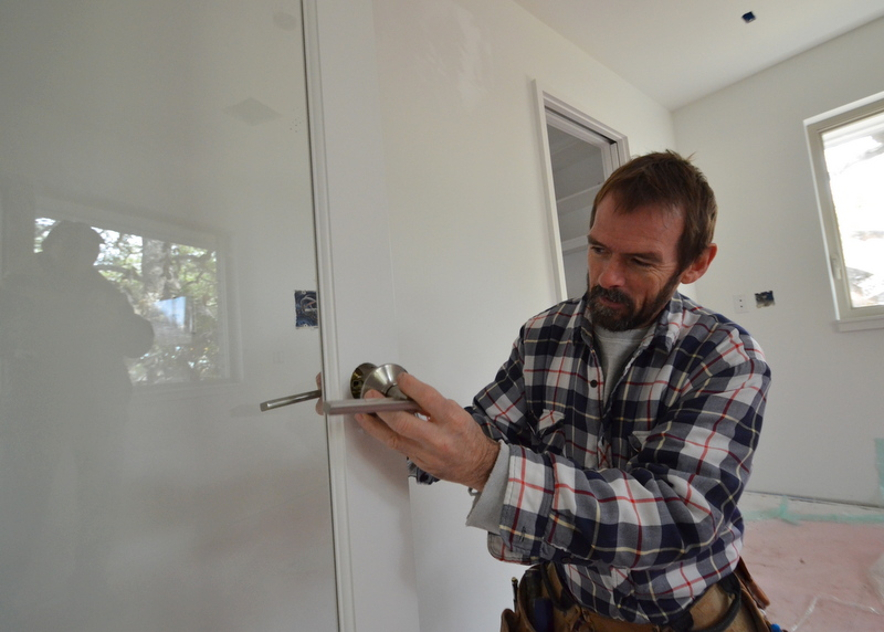 Shane installs the first door handle set -- on the door to Steven's office.