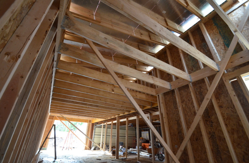 The horizontal beams are the ceiling above the parking bay and the floor of the storage loft above.