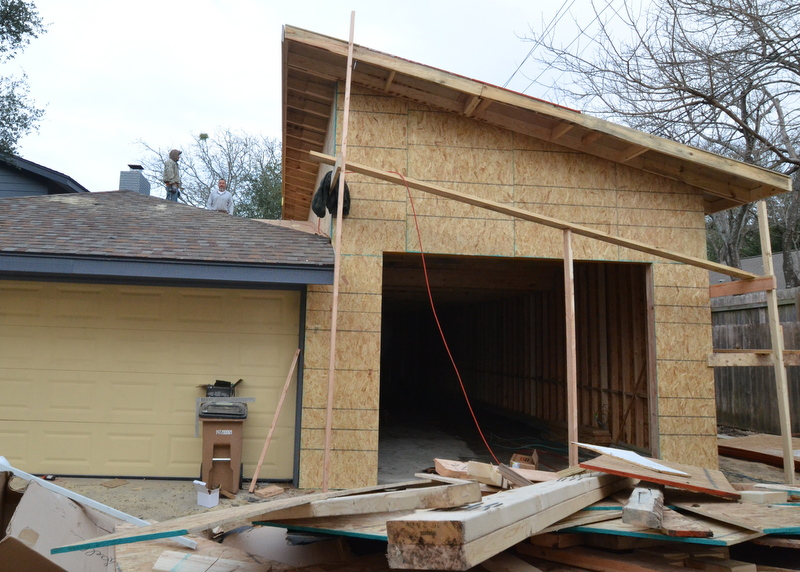 From the front. Where the old roof meets the new structure, the framers built a cricket to ensure that rainwater coming off the existing garage roof flows away from the vertical wall of the new structure.
