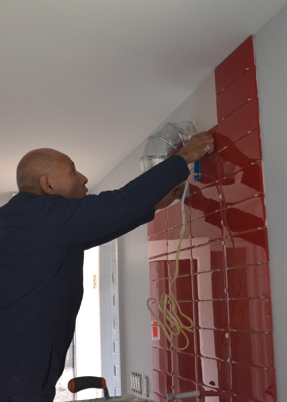 Julian works the glass tile around the exhaust fan and power outlet.