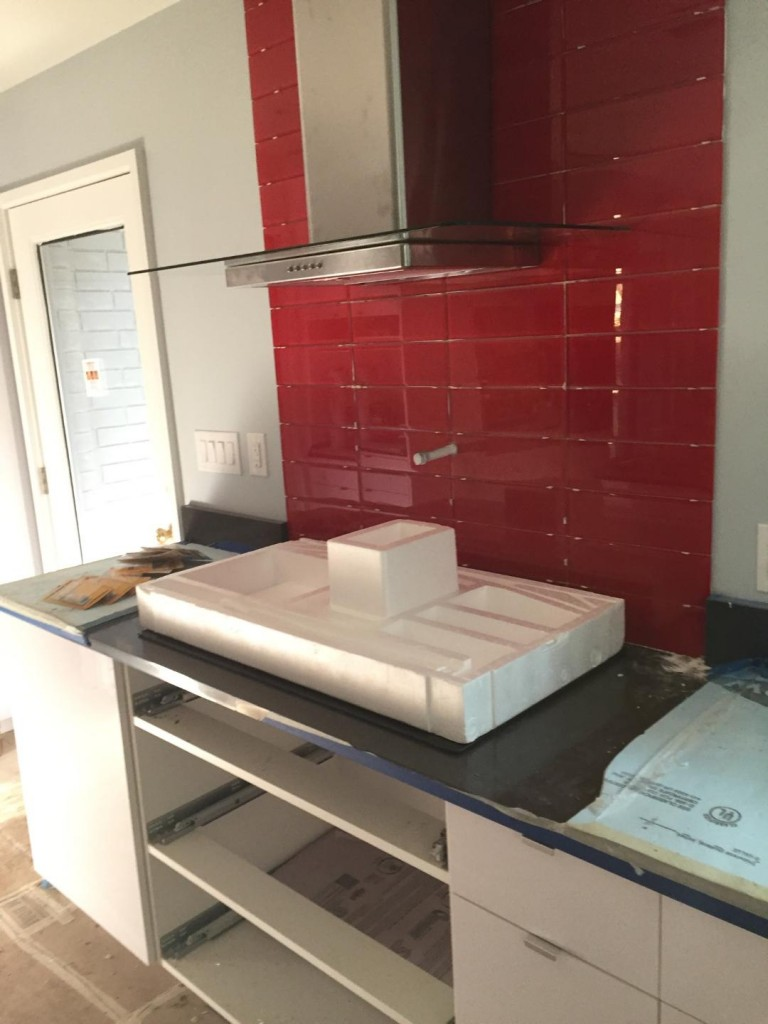 It looks like the exhaust hood is installed over the cooktop. Is the cooktop installed under the protective styrofoam? And look at that killer red backsplash.