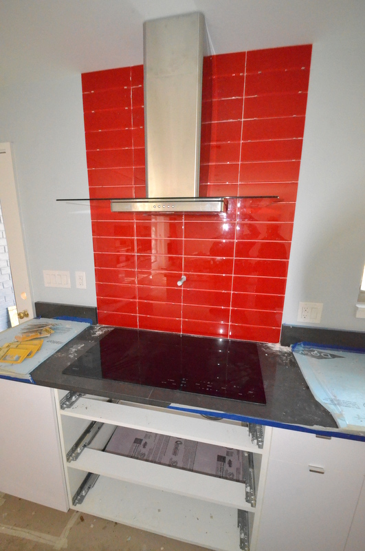 The heart of the kitchen -- appropriately red. Glass tile backsplash. Induction cooktop. Stainless steel exhaust hood. Pot filler not yet installed. Tile not yet grouted.