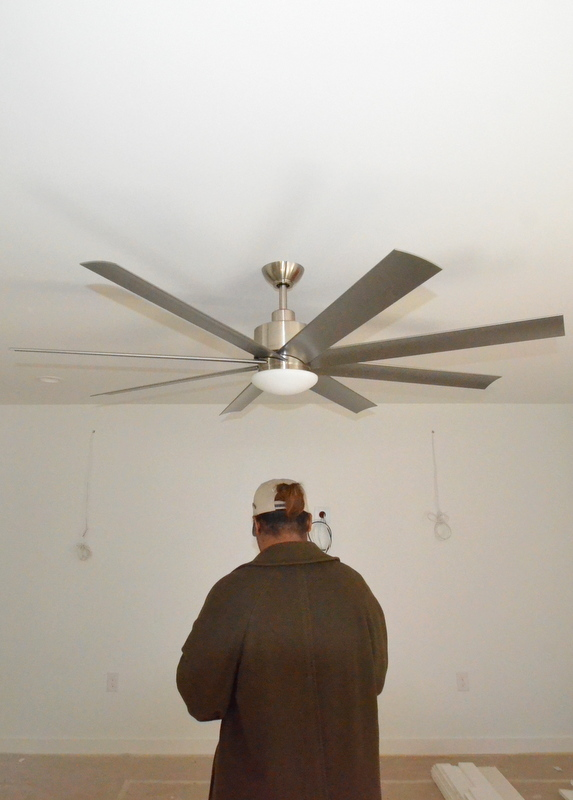 "The ceiling fan in the family room is too low. There's about one foot between the top of Jacquela's head and the bottom of the light kit. The ""problem"" may be the mounting post. It looks like it's six or eight inches tall. Steven remembers asking for a 3-inch post from Lights Fantastic. That shorter post would raise the fan closer to the ceiling -- which means Mark Rehberg from Ranserve, at six-foot-something tall, won't get a haircut if he walks under the fan while it spins. Something to discuss with Ron."