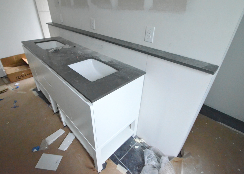 They mounted the undermount sinks in the master bath to the countertop with silicon and screws, trimmed the 4-inch deep gray quartz shelf to length and glued it into position behind the vanity ...