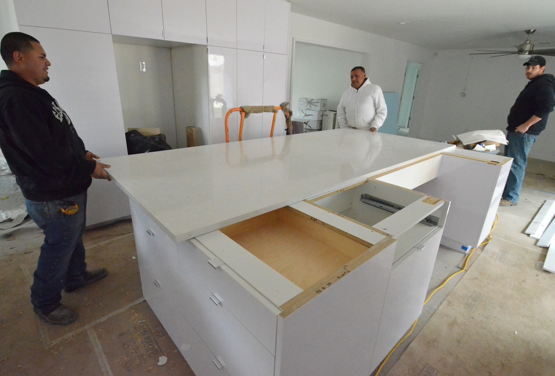 3. They slid the 5x10-foot slab of quartz off the base cabinets while Matt, at right, watched ...