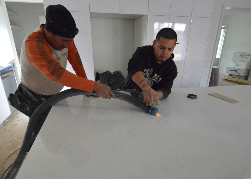 Miguel drills the countertop for the electrical outlet while Luis suctions away quartz dust.