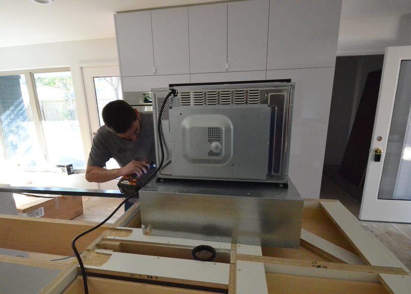 Arnold screws the storage drawer and microwave together to create a single unit.