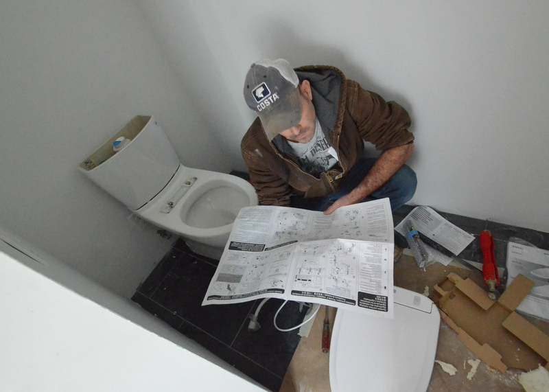 Mike studies how to install the Toto toilet and bidet in the master bath -- and the magic, proprietary $45 Toto pipe.