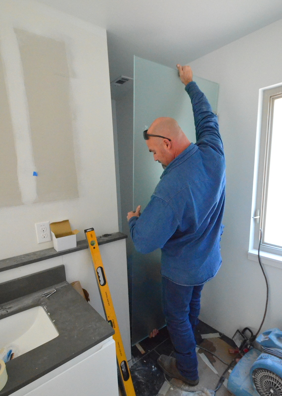 Chris attempts to lever into place the frosted and tempered glass door to the water closet in the master bath. Billy is inside the water closet working the bottom of the door into position. They discover that the glass is about 1/4 inch too wide; it was measured incorrectly.