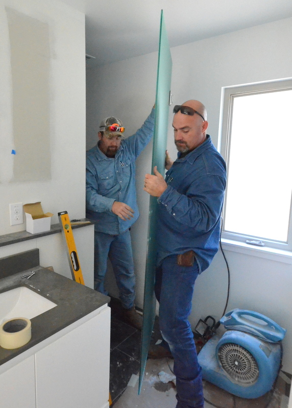 Billy, left, and Chris, walk the oversized glass door out of position. After this, they measured the passage several times, using several tape measures, to confirm the glass is 1/4-inch too wide. They marked the correct widths on the glass door, carried it downstairs and out to the truck to take away. Because the glass is frosted and tempered, it cannot be trimmed or cut to proper size. They order a replacement. Chris says it will take about a week to arrive.