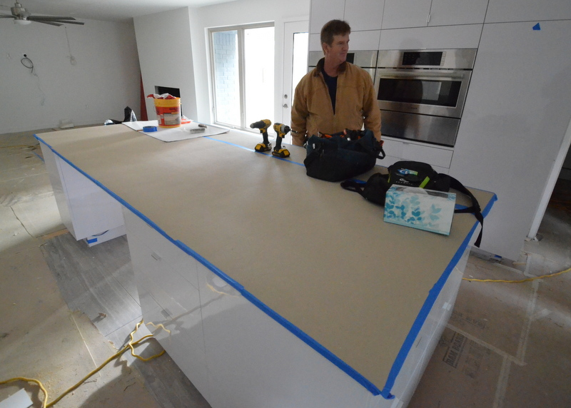 In the kitchen, the quartz countertop is reinstalled to the island. That's Ron Dahlke, supervising his kingdom.