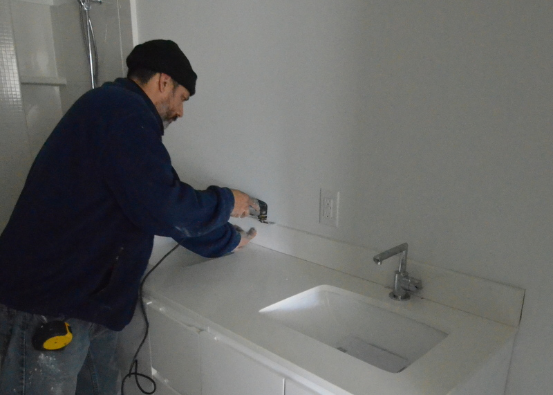 Upstairs in bath 3, Cris deploys the multi-tool to cut around the backsplash. He will remove the drywall from this location, as he did in bath 2, then inset the backsplash quartz into the wall, allowing the faucet handles to swing through a complete arc without obstruction.