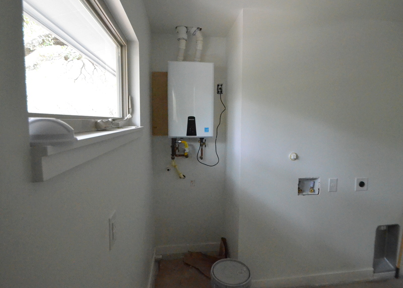 The tankless water heater is installed upstairs in the laundry/utility room.