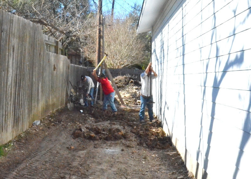 At the rear of the garage, Gilsa is regrading the dirt to ensure water runs off away from the garage foundation. This entire strip of bare dirt will be covered with weed block fabric and then black gravel.