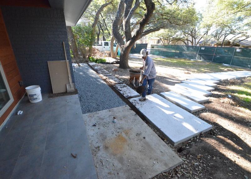 About an hour later, the gravel extends to the front porch and dirt is going in between the concrete pavers.