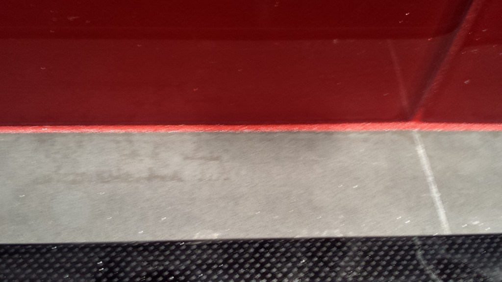 "A close up of the ""bleed"" between the glass-tile backsplash and the gray quartz countertop. This line should have been caulked with gray silicon, not the red grout."