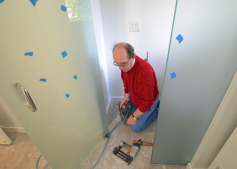 Peter reinstalls trim in the water closet to bath 2. The glass installers removed this trim to put in the oversized glass door and fixed panel.