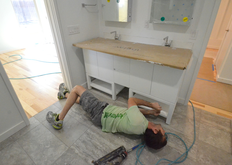 Shane gets prone on the floor of bath 2 and reaches under the vanity to install a missing baseboard. Tight fit, but committed. Power tools are too large to squeeze under the shelf.