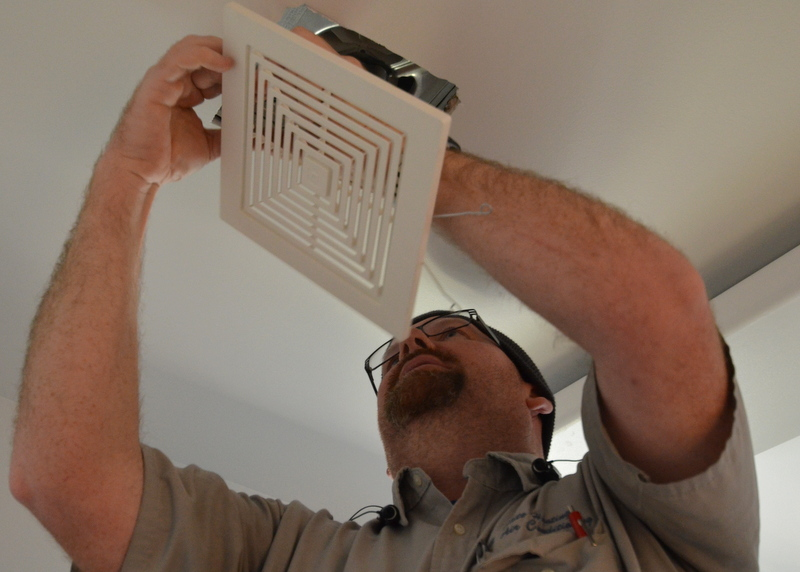 DJ from Elite Air Conditioning arrived with baffles, bulbs and grilles for bathroom ventilation. Here he hooks the grille to the exhaust fan in the ceiling of the laundry room -- after first installing the fan module and motor.