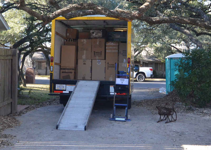 The back end of the rental truck with unloading already underway. This is as far as we could back the truck without colliding with the oak tree.