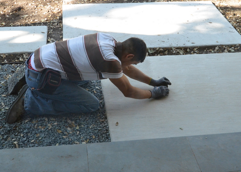 Rodriguez from Gilsa uses a chunk of concrete to grind stains off the first paver in front of the house.
