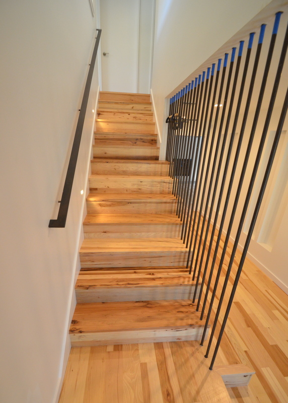 Noemi and her team took the protective cardboard off the stairs, cleaned up the construction mess, to reveal a work of art -- hickory risers and treads, steel balusters and handrail, stair lights recessed into the wall.