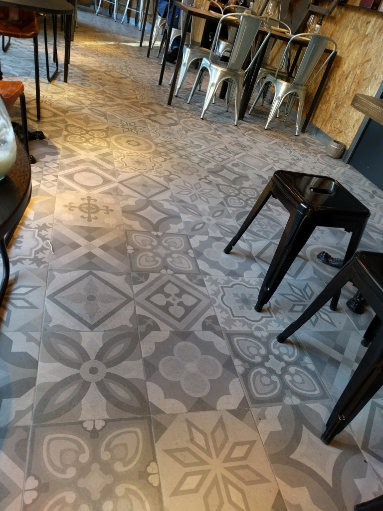 "This is the floor of the restaurant where I ate lunch one day in Barcelona while traveling for ShowStoppers @ MWC 2016 -- concrete tile, bold patterns, vivid with life, you'd never know it was ""boring gray."""