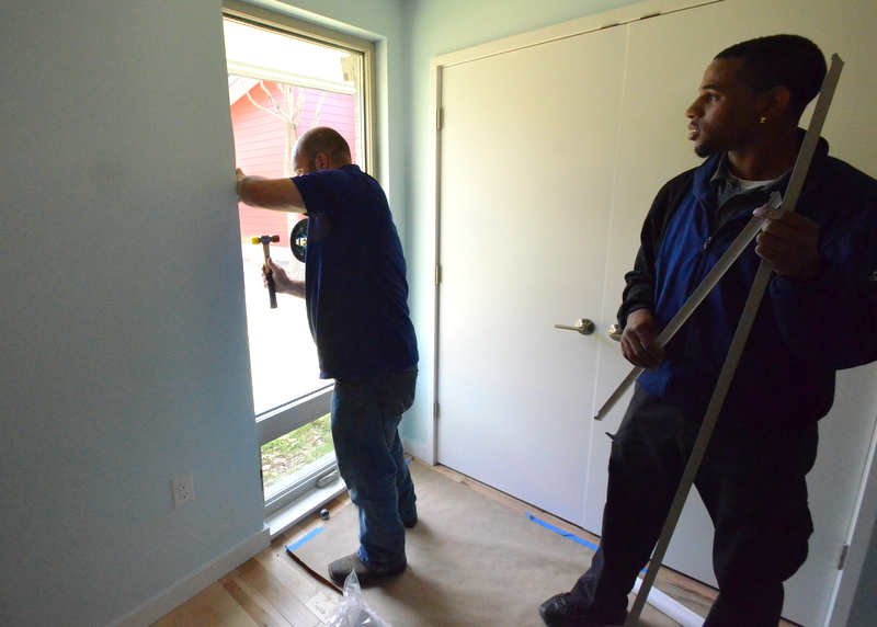 Landon taps the window trim into place as Robert sorts the next trim piece to install.
