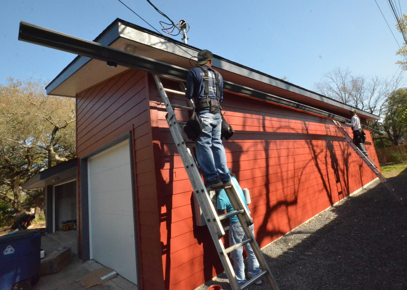 Alex, left, and Grigorio, right, hoist the gutter into position at the low end of the shed roof over the new garage.