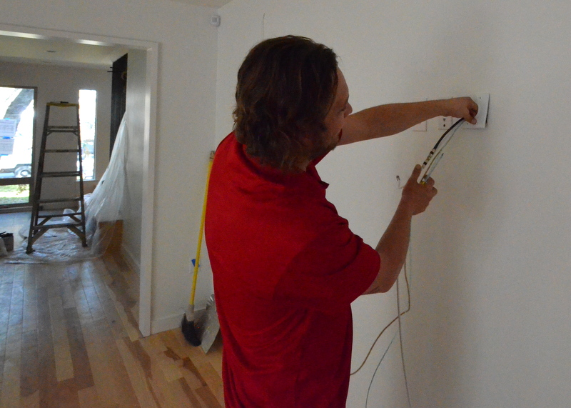 Tyler from Granite Security installs a network wall plate at the TV wall in the family room.