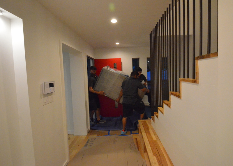 Squeezing the washing machine through the front door and up to the stair landing.