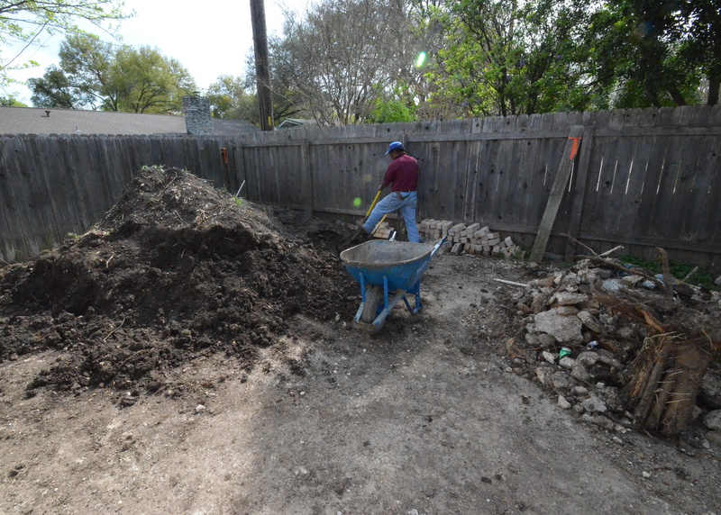 Outside, Victor and Ramon are shoveling down off the driveway the really good black dirt   piled up when Gilsa and Ranserve dug out the foundation for the new garage bay. Here's Ramon late in the afternoon shade, spading deliberately in the record March heat -- 91 degrees.