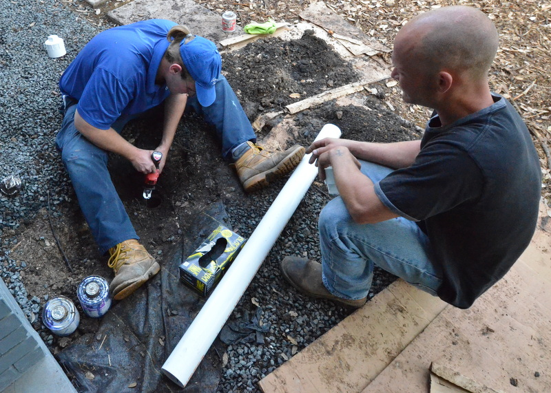 Noah attempts to cut away corrosion from the metal pipe that was buried for some part of nearly 50 years using a cordless reciprocating saw and blade. Tim prepares the new PVC that will be inserted into the buried pipe.