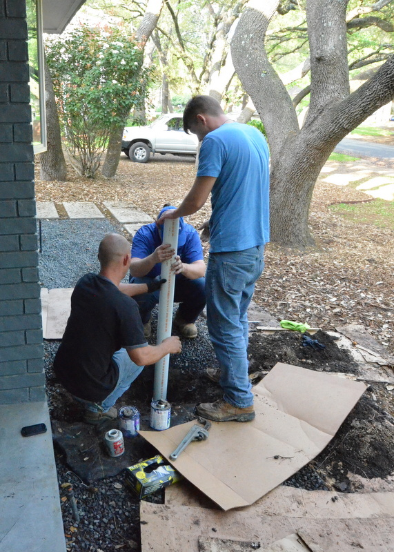 Tim, left, Blake, right, and Noah, hidden, force the new PVC into the old pipe junction. After this, they shoveled dirt back into the excavation, then gravel on top of the dirt, capped the new PVC, and cleaned up everything.