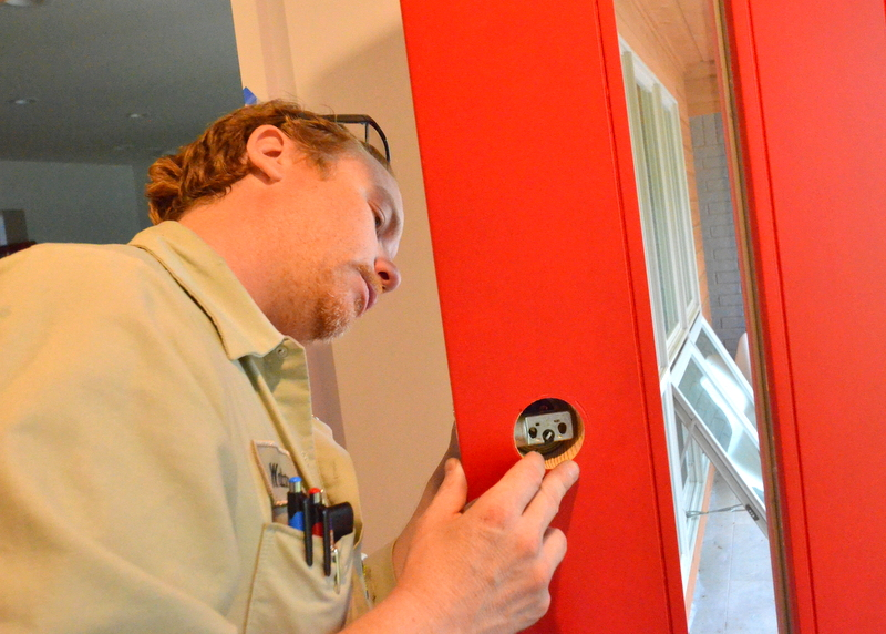 When the pins are all correctly assembled, Walter puts each lock assembly back together in reverse order of disassembly. Here, he reinstall the lock mechanism to the front door. As Walter finished with each door, Steven tested one key in each of the five locks, to ensure that all five operated with that one keyset.