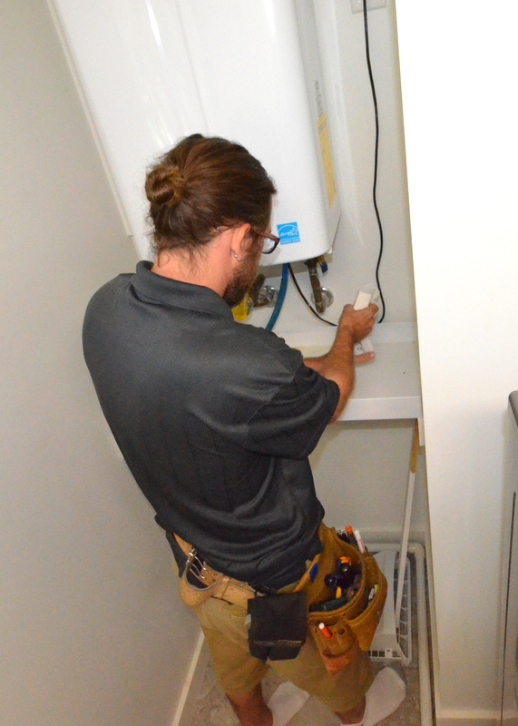 Chris positioning the water bug at the upstairs tankless water heater.